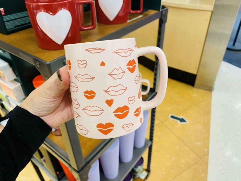 hand holding a Starbucks Kisses Mug