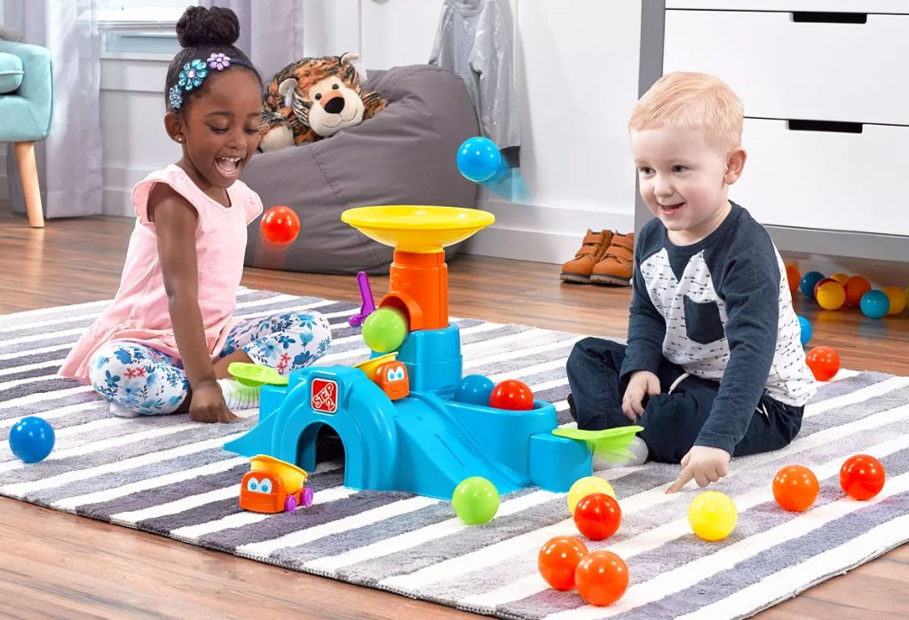 boy and girl sitting on floor in playroom playing with colorful tower tunnel toy with play balls