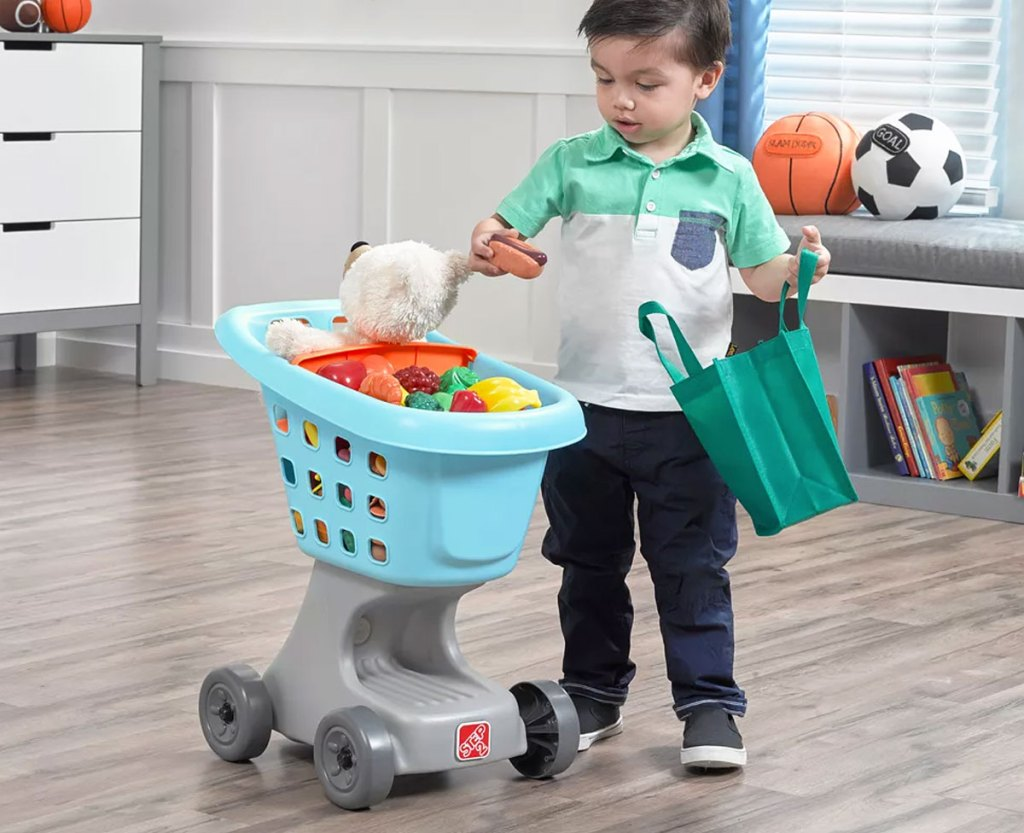 boy grabbing plastic food items from blue shopping cart to put them into green reusable shopping bag