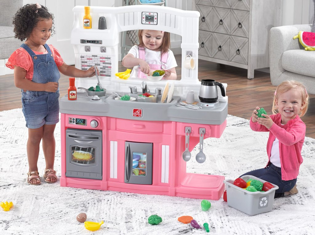 three girls in playroom playing with white and pink kitchen set with food items all over the floor