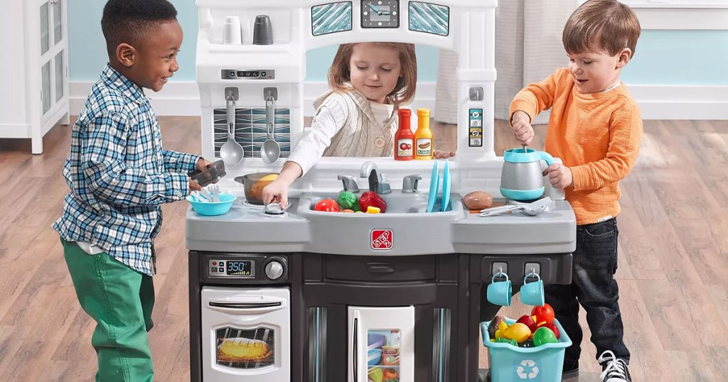three kids in playroom playing with a play kitchen set