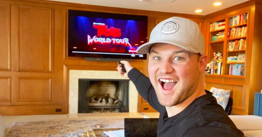 Pria bertopi abu-abu dan kemeja hitam menunjuk remote ke TV menonton film Trolls World Tour