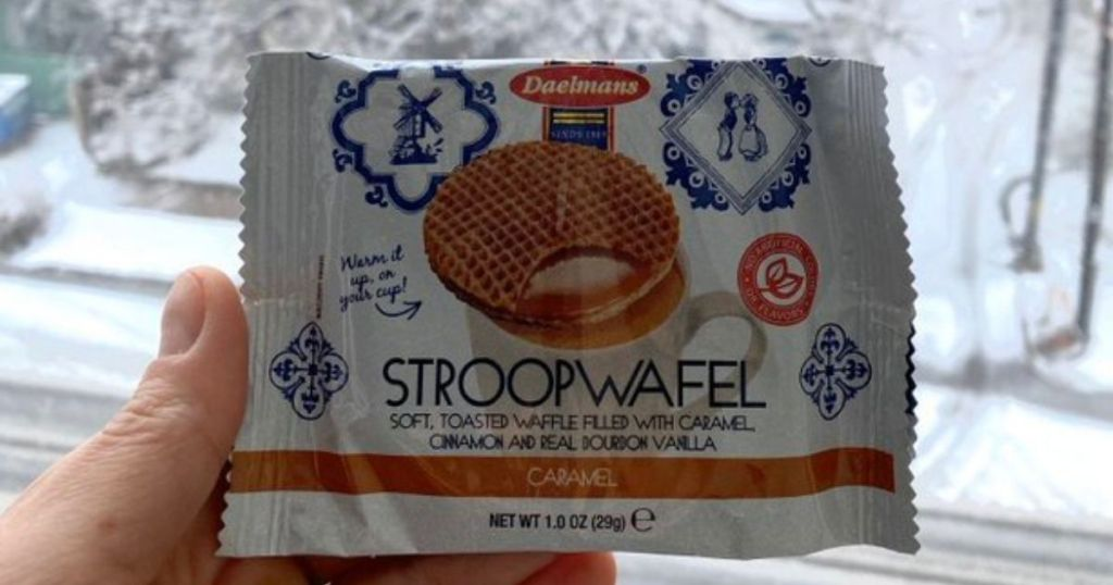 hand holding Stroopwafel with snowy background