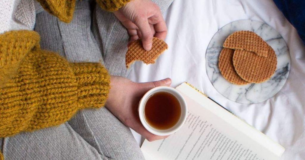 hand holding half eaten stroopwafel and tea in other hand