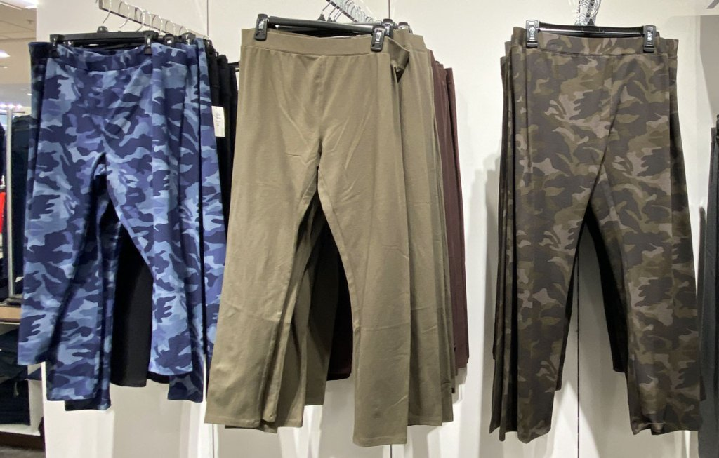 three pairs of women's leggings in blue camo, green camo, and solid olive green colors on hangers hanging on a display wall