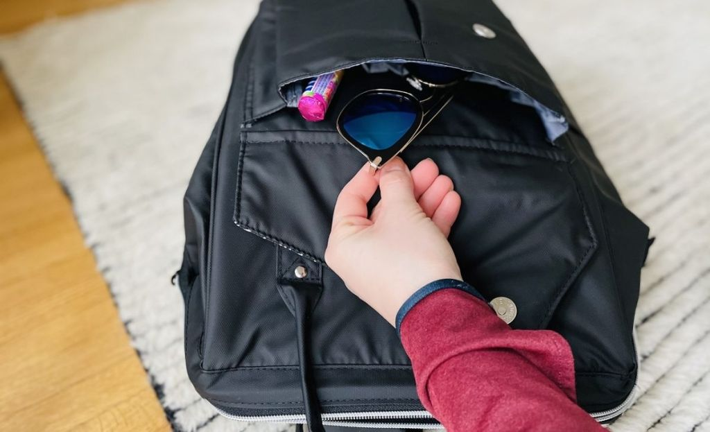 A hand placing some sunglasses in a backpack