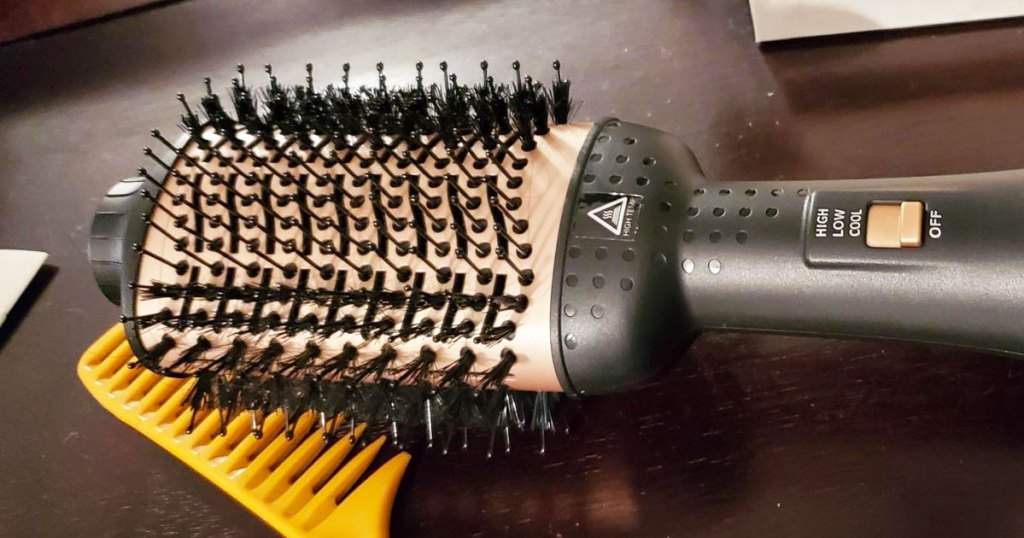 black and gold hair dryer brush on a wood table next to a yellow comb