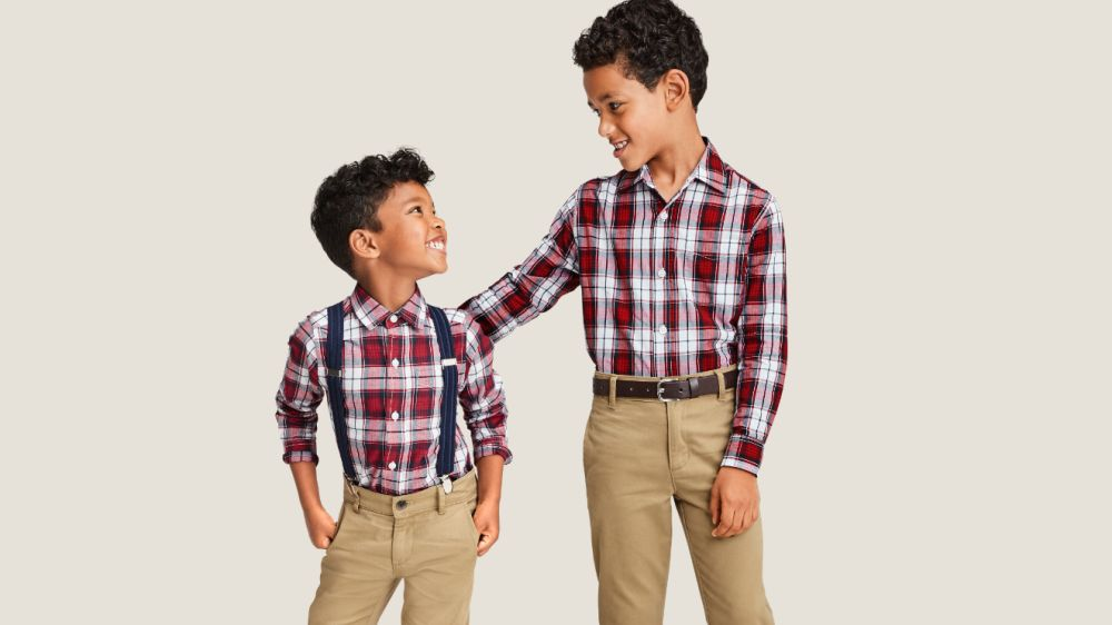 two boys standing together in matching outfits