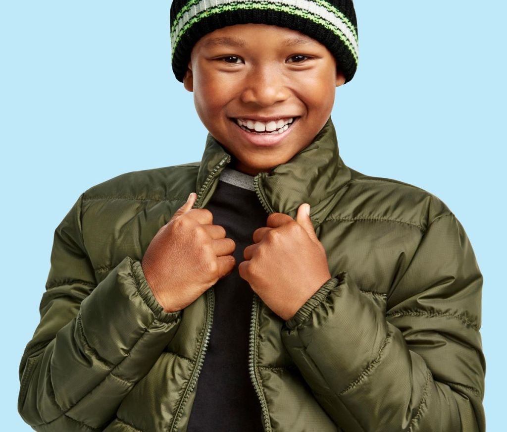 boy smiling and wearing a puffer jacket