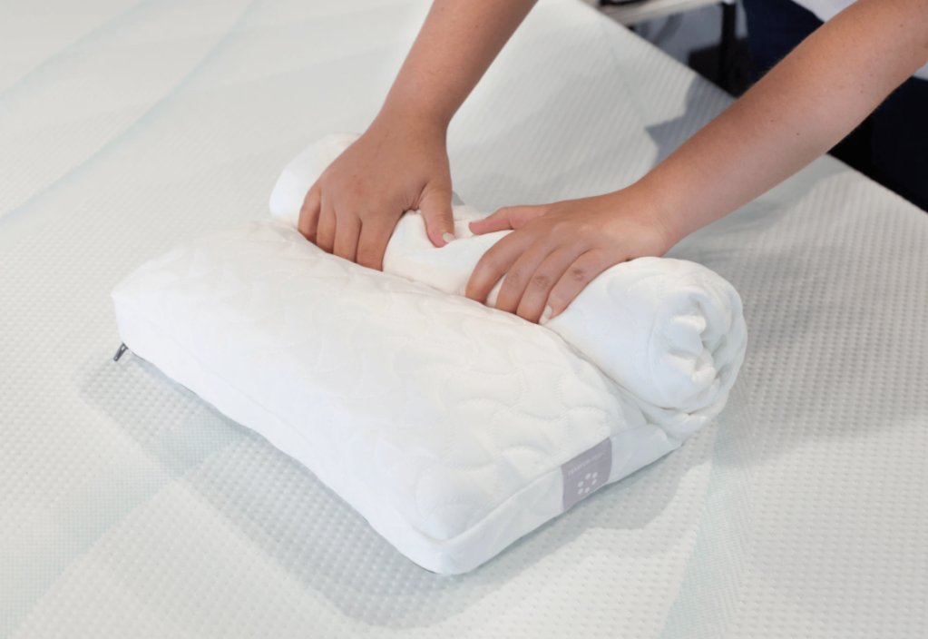 person rolling up a pillow