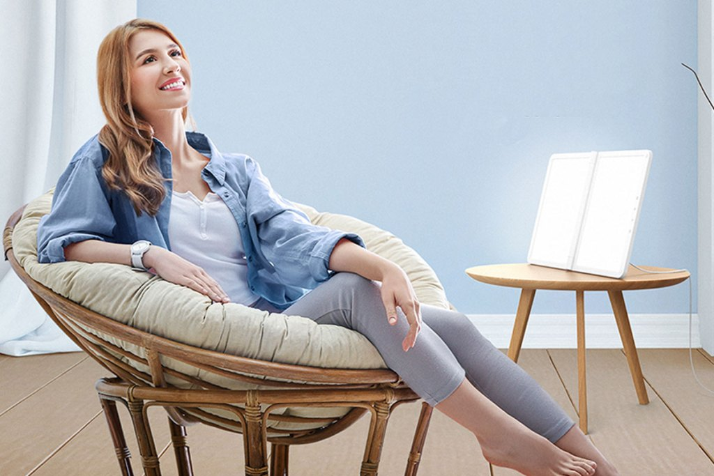 woman sitting in papasan chair with a light therapy light placed on side table shining at her