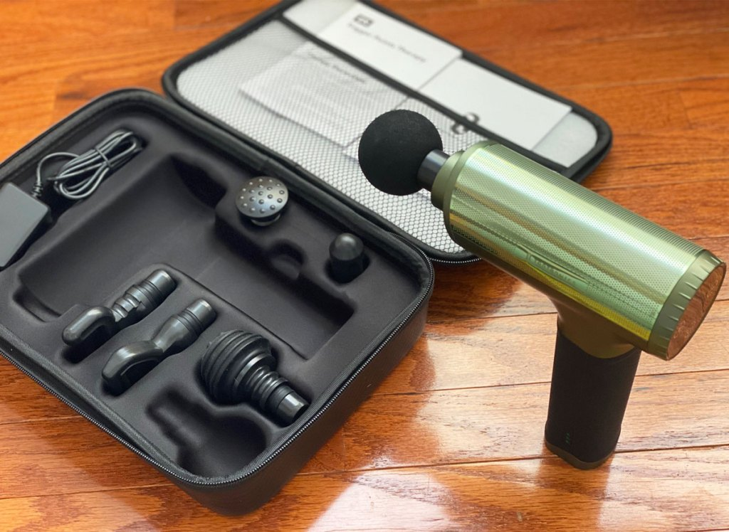 green and black massage gun on a wood table with an opened black case holding multiple attachments for it