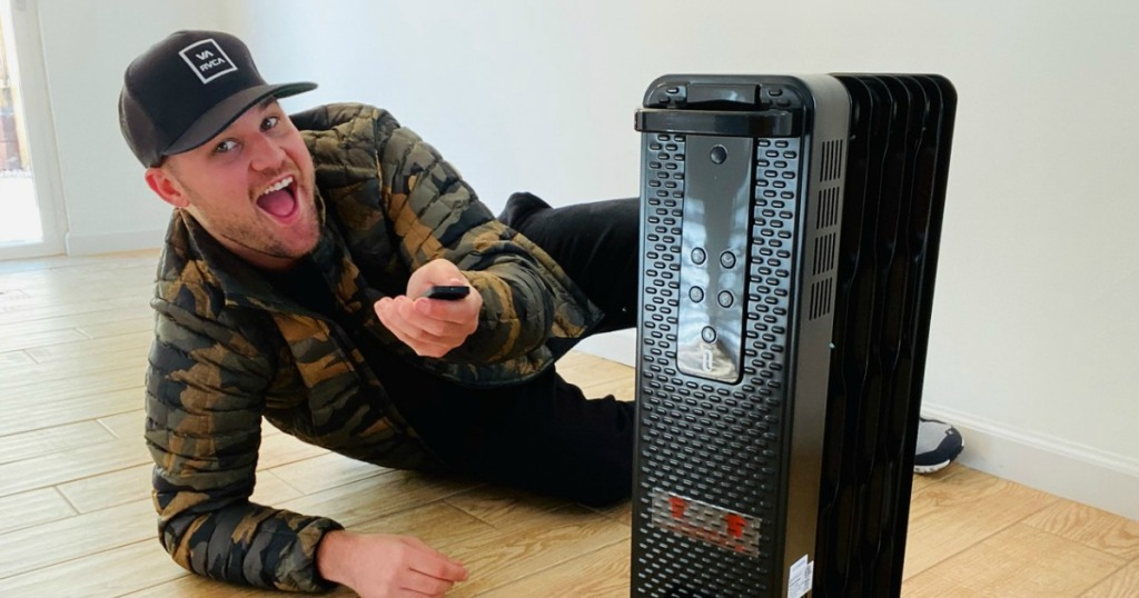man holding remote behind a space heater