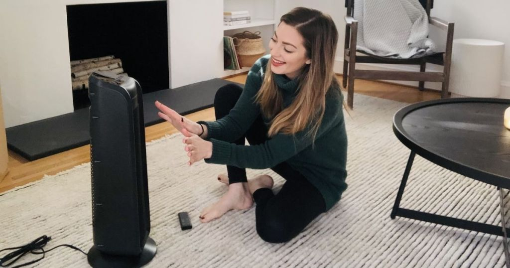 woman sitting on floor with hands out in front of space heater