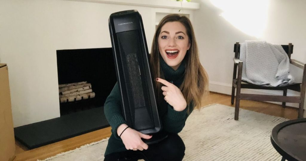 woman holding black space heater in one hand and pointing at it with her other hand