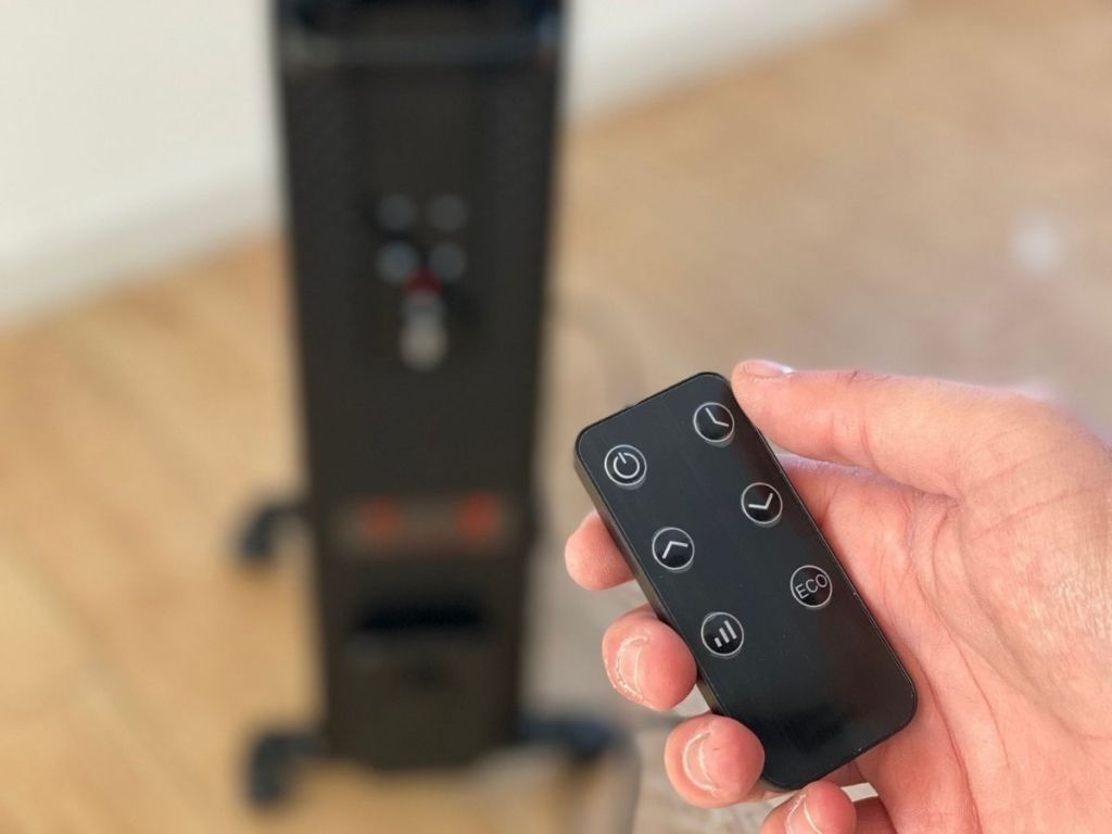 hand holding remote with black heater blurred in background