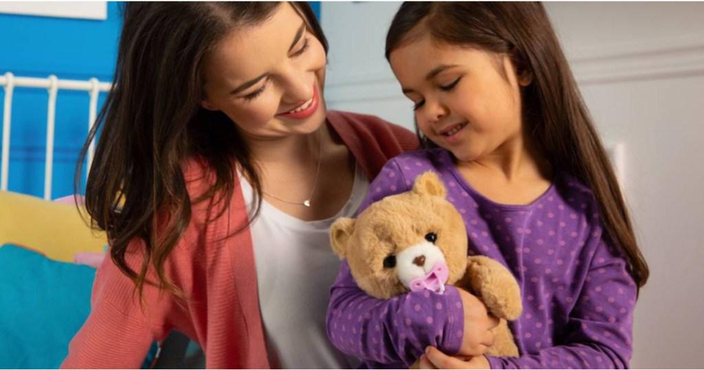little girl holding a little live teddy bear next to a woman