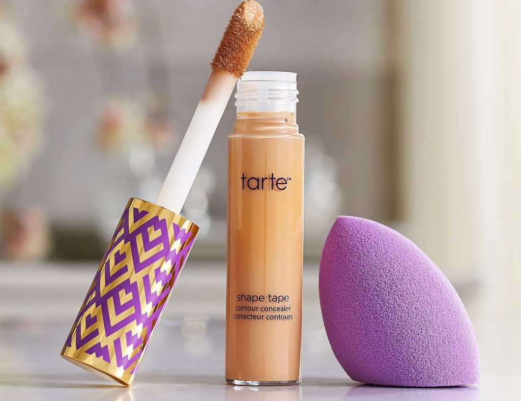 bottle of tarte spade tape with wand leaning against it and purple blending sponge