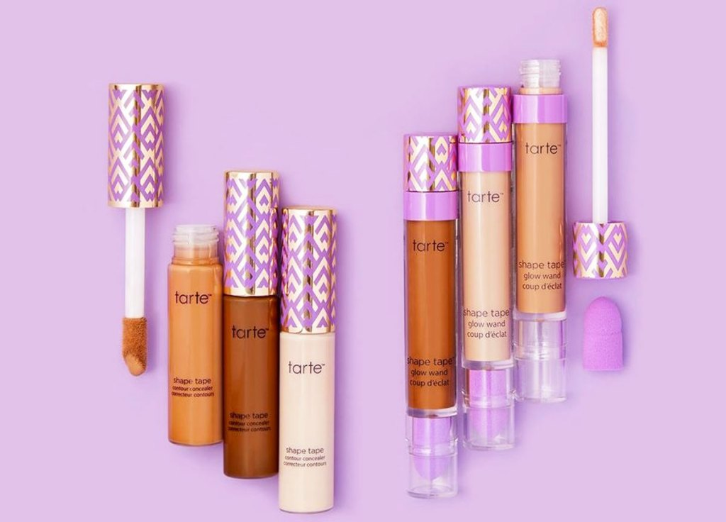 bottles of tarte shape tape and glow wands on a purple background