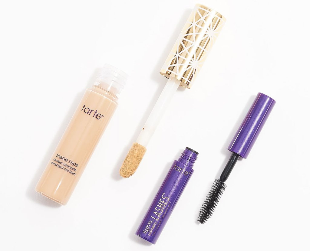 bottle of tarte shape tape with gold printed lid and purple travel-size mascara
