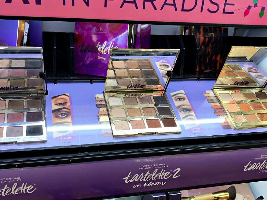 three Tarte eyeshadow palettes on display at a store