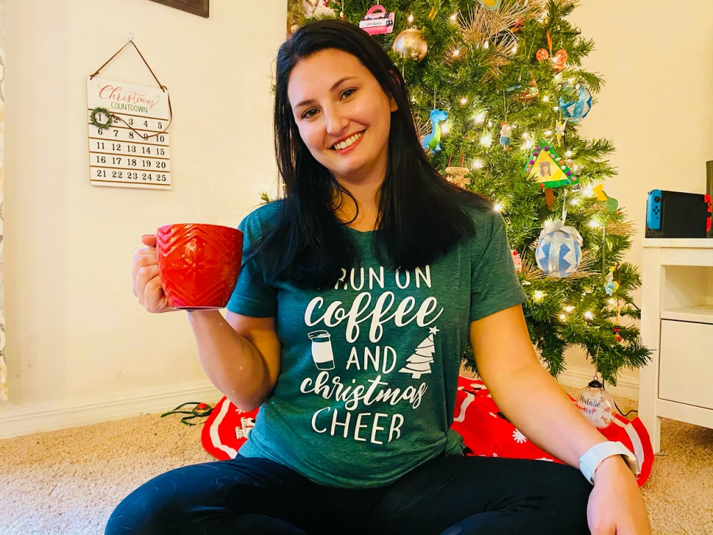 woman holding a coffee cup sitting in front of a Christmas tree