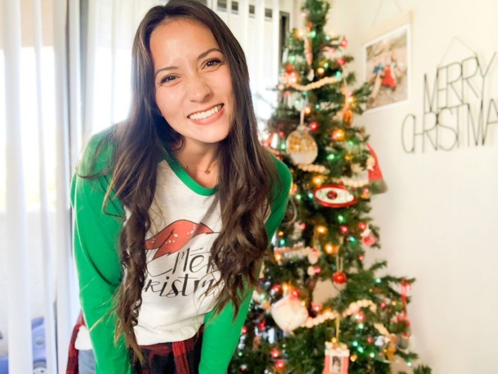 woman standing in front of a Christmas tree and smiling at the camera