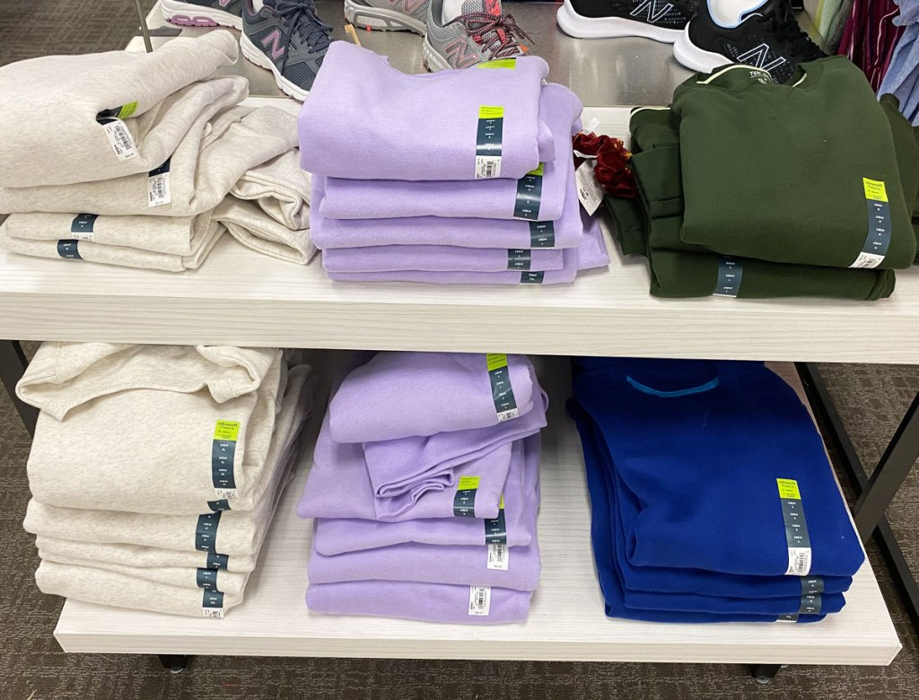 cream, lavender, navy blue, and dark green stacks of folded sweatshirts on a white display shelf