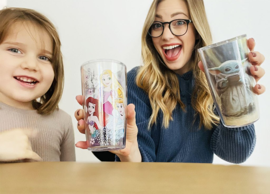 blonde woman and little girl sitting at table holding disney and star wars tumblers
