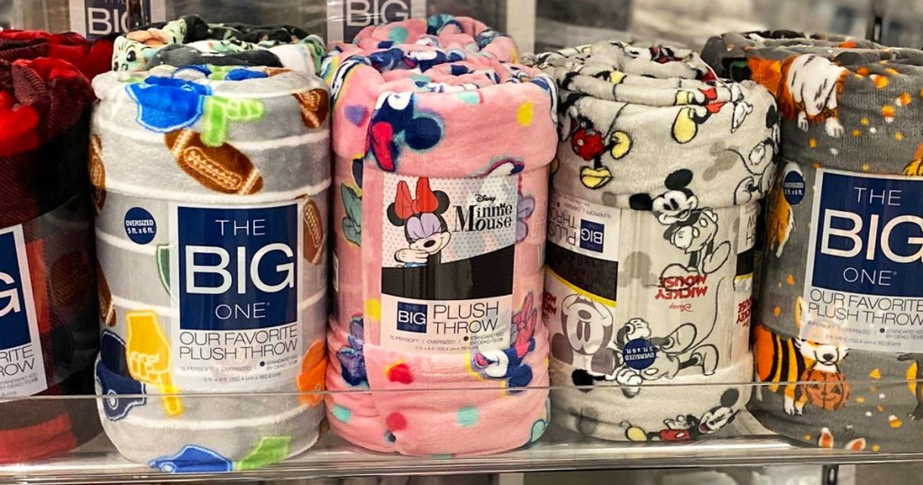 the big one throw blankets in football, mickey, and minnie mouse prints on a store display shelf