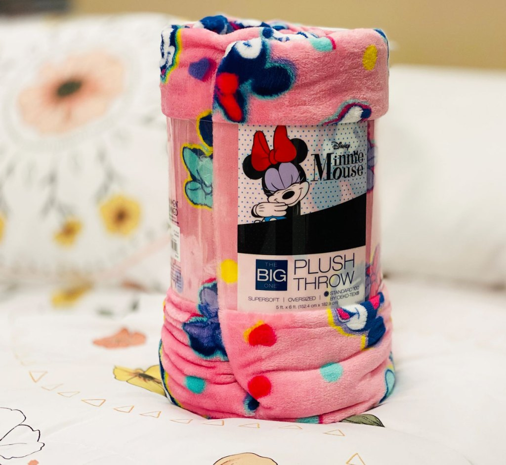 rolled up pink minnie mouse print throw blanket sitting on a bed