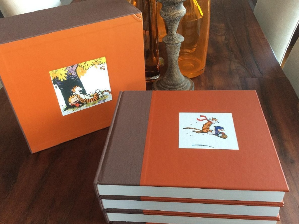 three large books and box set container on table