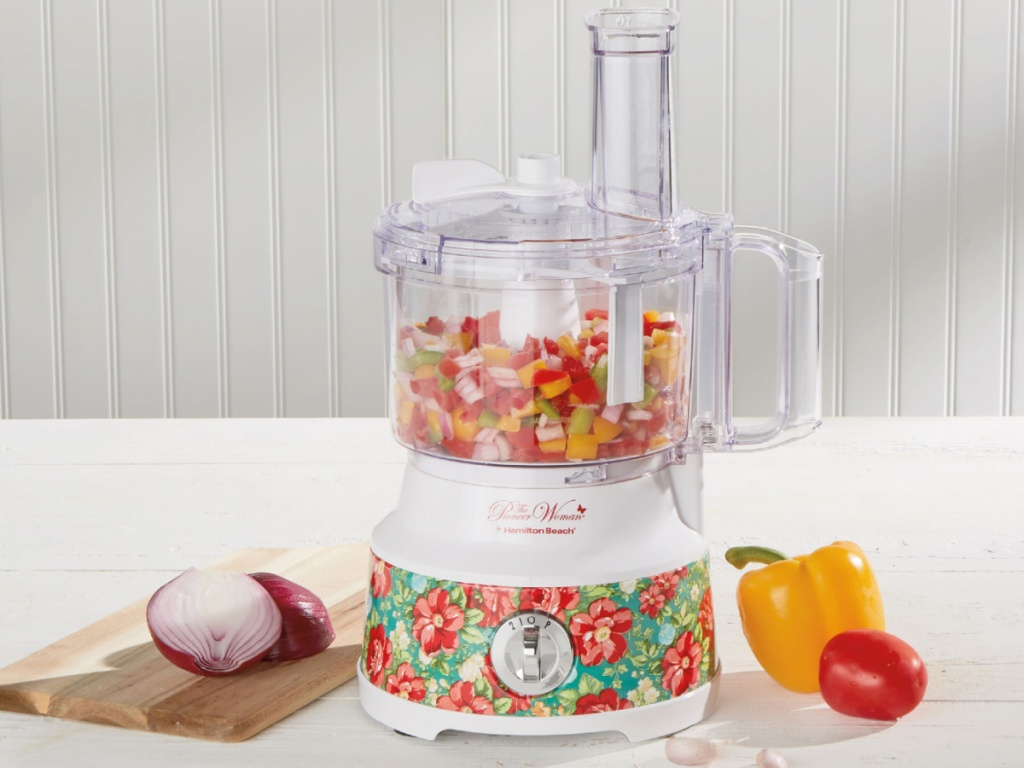 floral food processor filled with food on counter, cutting board, onions, and peppers