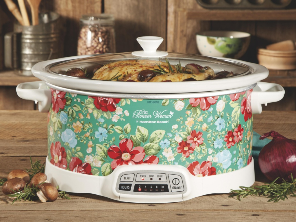 floral slow cooker filled with food on wood table