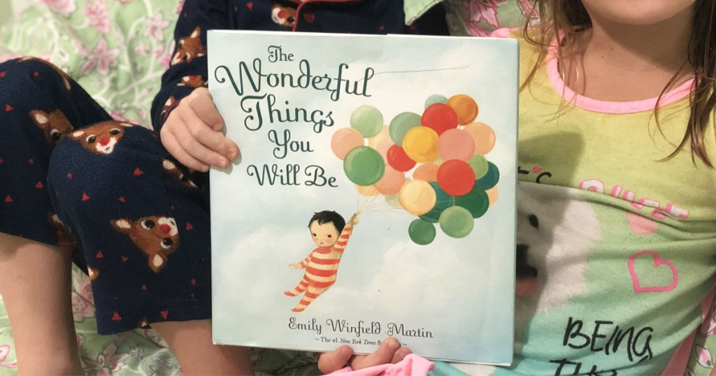 boy and girl holding up The Wonderful Things You Will Be hardcover book