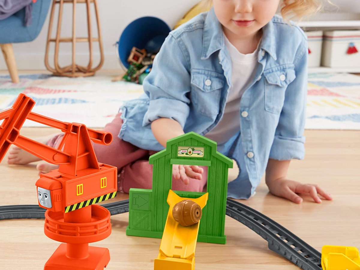 girl playing with train set on floor