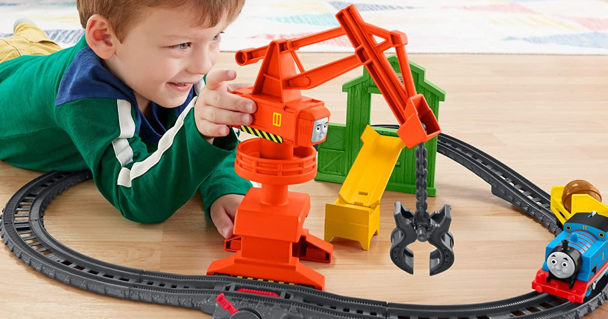 boy playing with train set on floor