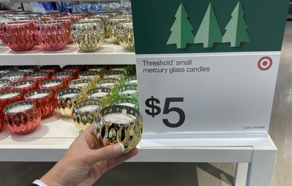 various Christmas themed candles on store display table