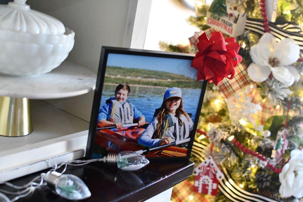 foto berbingkai duduk di rak dekat pohon Natal