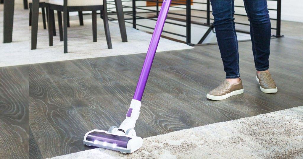 Wanita dengan jean dan sepatu kets emas menggunakan penyedot debu tongkat ungu dan putih untuk membersihkan kayu keras dan lantai berkarpet