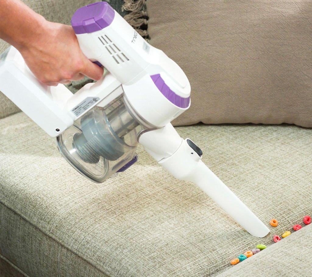 orang yang menggunakan penyedot debu genggam berwarna putih dan ungu untuk membersihkan sereal buah dari sofa