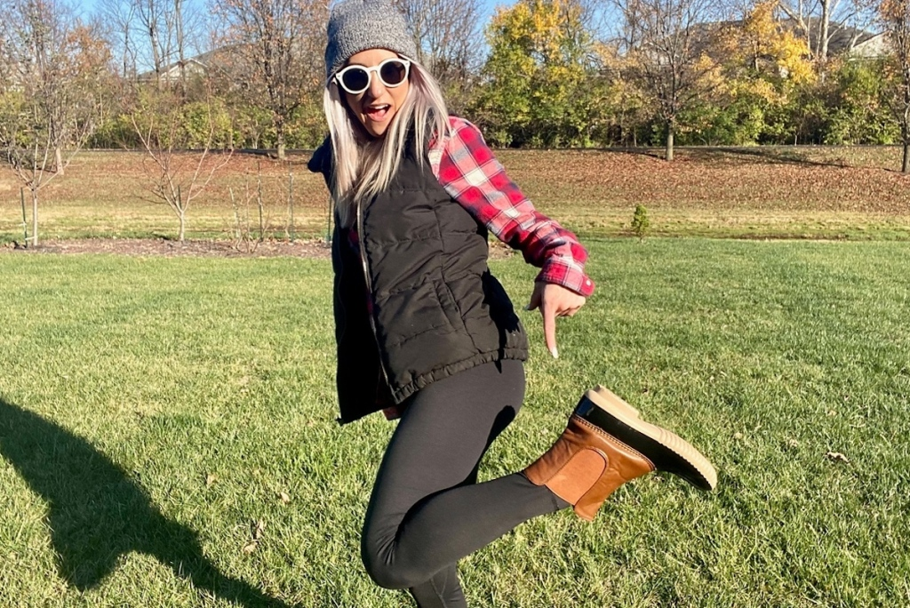 woman pointing to duck boots standing in grass