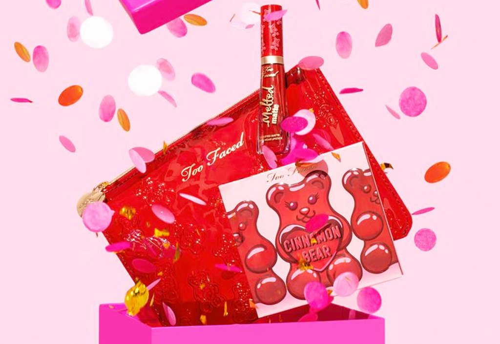 pink box opening with confetti falling out with red makeup bag, cinnamon bear eyeshadow palette, and liquid lipstick