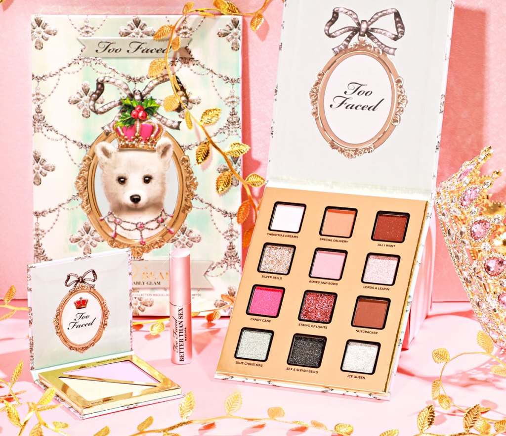 too faced eyeshadow palette, highlighter, and mini mascara on a pink table with gold leaves and gold crown next to them