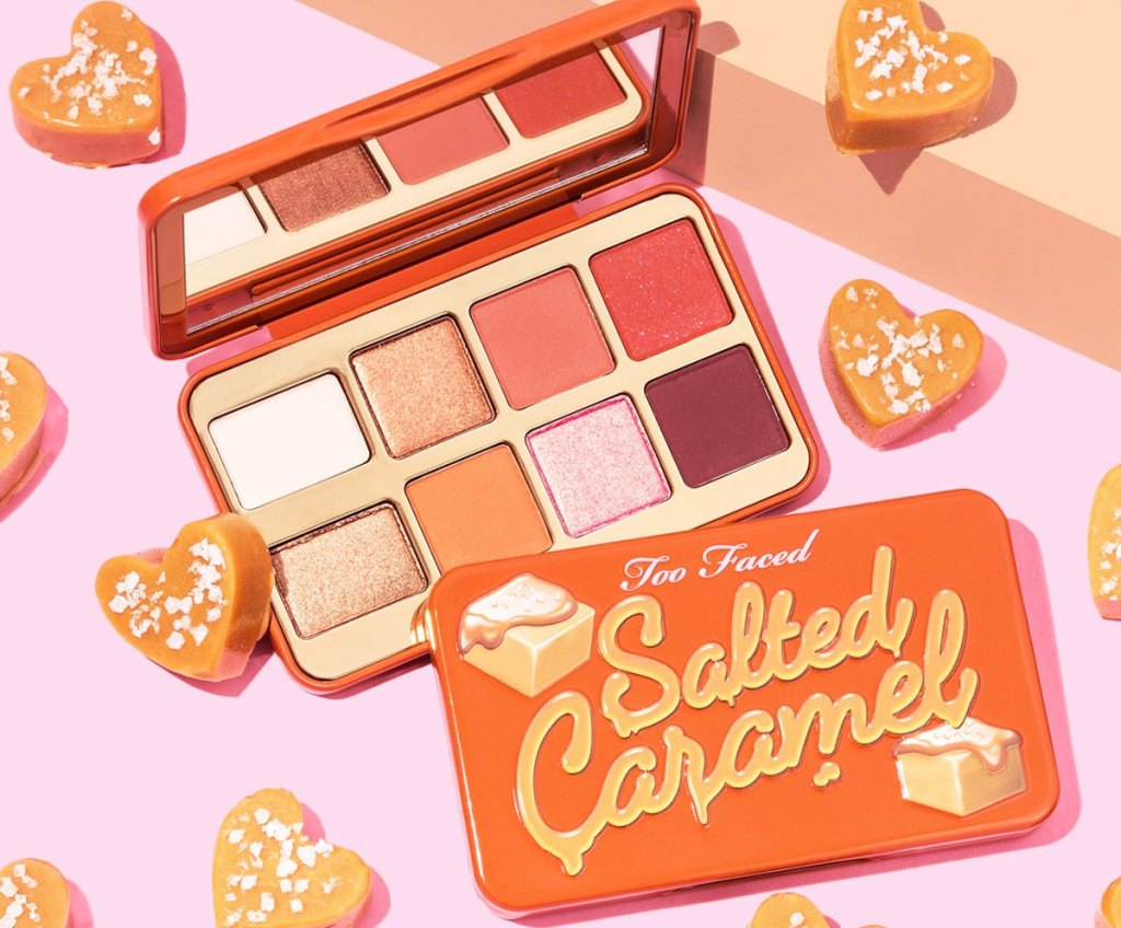 too faced salted caramel mini eyeshadow palette on a pink background with heart shaped caramel candies around it