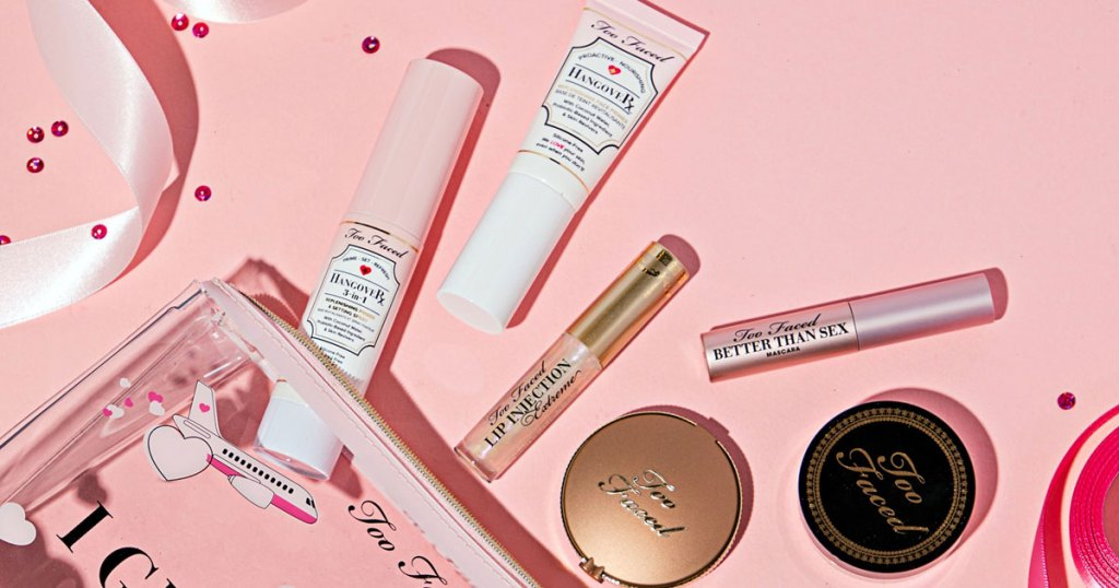 too faced travel size cosmetics coming out of a makeup bag on a pink background