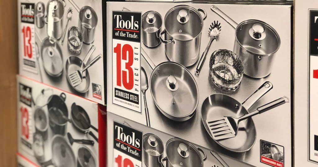 boxes of Tools of the Trade 13 piece stainless steel cookware sets stacked on one another at Macy's