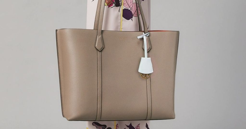 woman carrying a tan tote