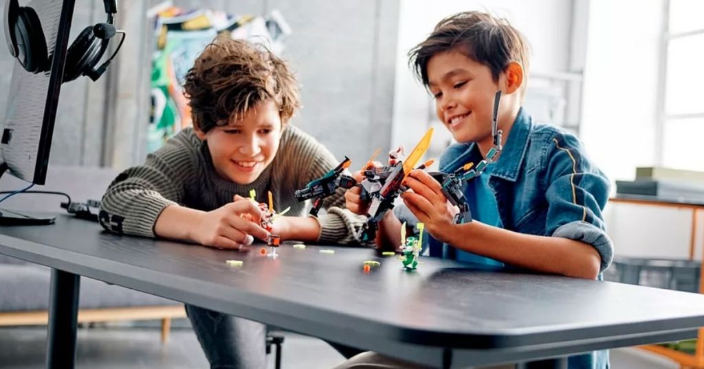 two boys sitting at a table playing with a lego ninjago set