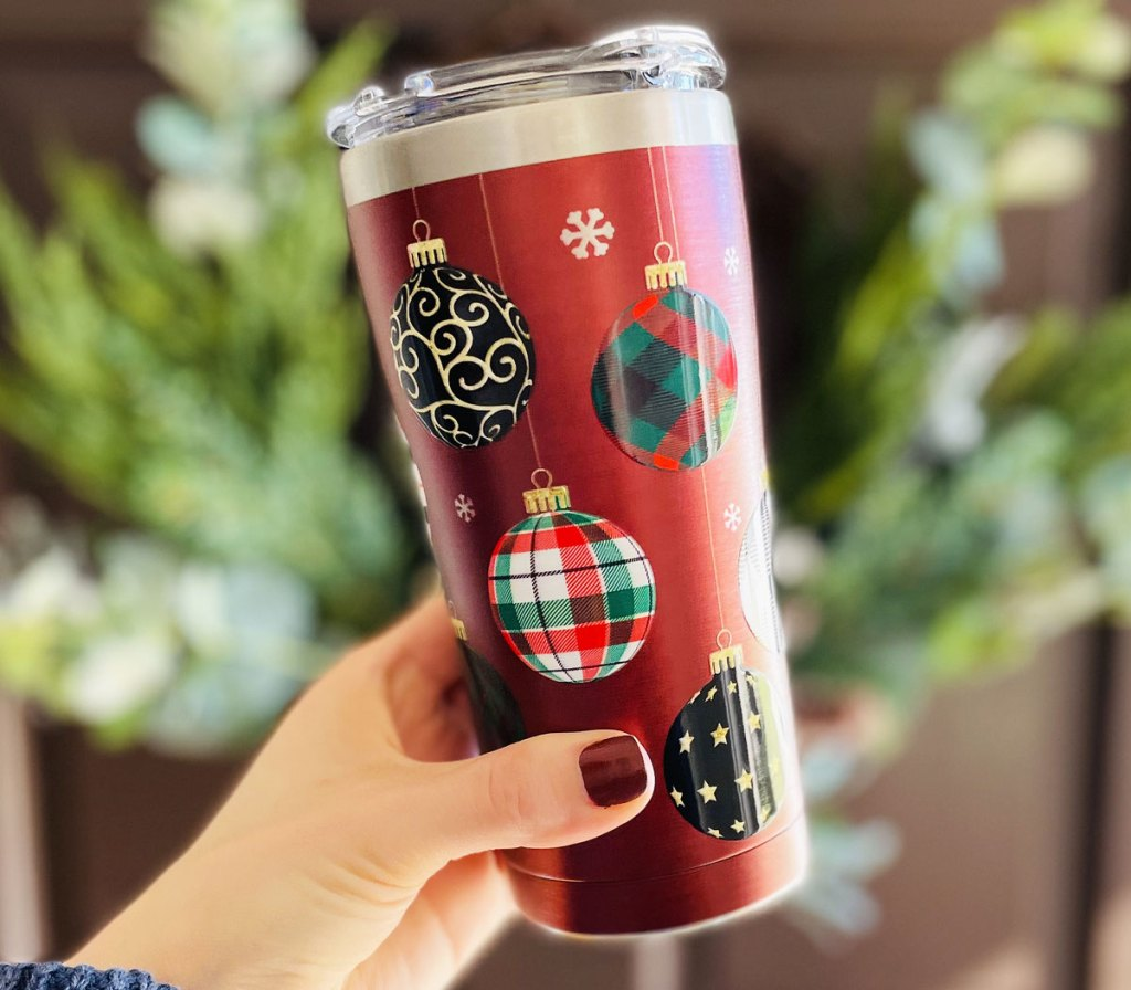 woman holding up red christmas themed tumbler with wreath in background